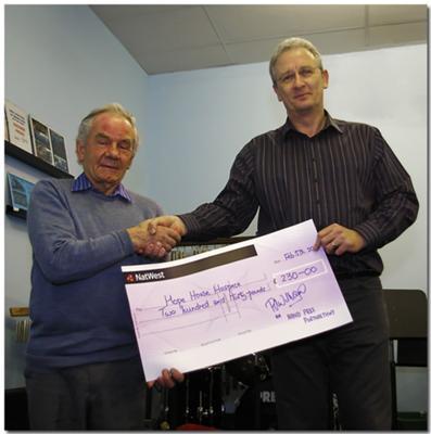 Arthur Newnes (left) receiving the cheque on behalf of Hope House from Menai Bridge Band Chairman, Brian Mottershead